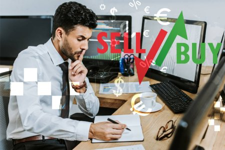 Photo for Pensive bi-racial trader writing in notebook and sitting at table near sell and buy letters - Royalty Free Image