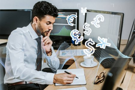 Photo for Pensive bi-racial trader writing in notebook and sitting at table near money signs - Royalty Free Image