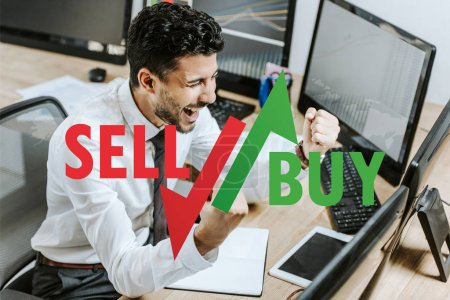 Photo for Happy bi-racial trader showing yes gesture near computers, sell and buy letters - Royalty Free Image