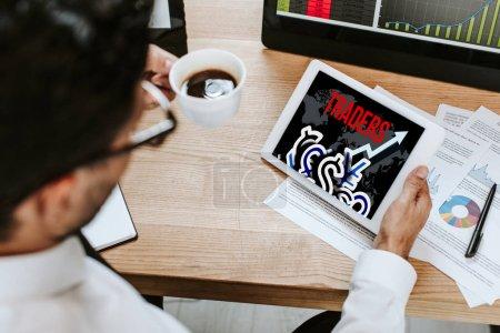 Photo pour Focus sélectif de l'homme tenant la tasse et la tablette numérique avec les commerçants lettres - image libre de droit
