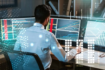 back view of trader working near computer with graphs