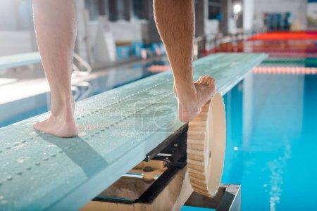 Photo pour Vue recadrée du nageur debout sur le plongeoir - image libre de droit
