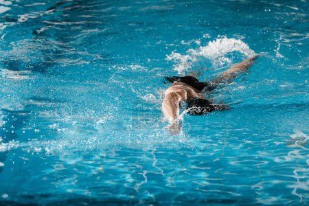 Photo for Athletic man diving in swimming pool with blue water - Royalty Free Image