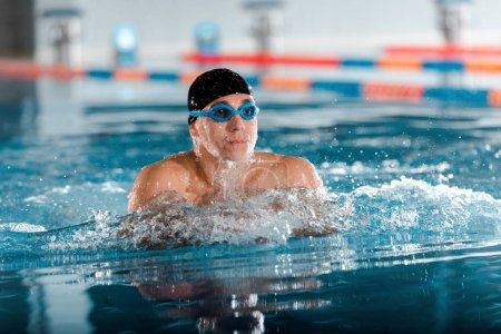 Photo for Selective focus of handsome athletic man in goggles and swimming cap in swimming pool - Royalty Free Image