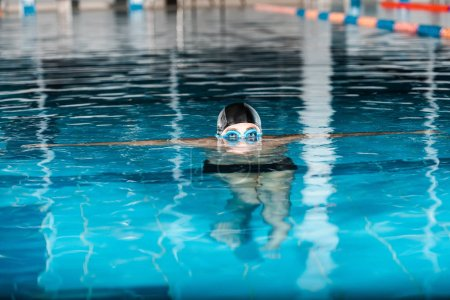 Photo for Cropped view of swimmer in swimming cap and googles in water - Royalty Free Image