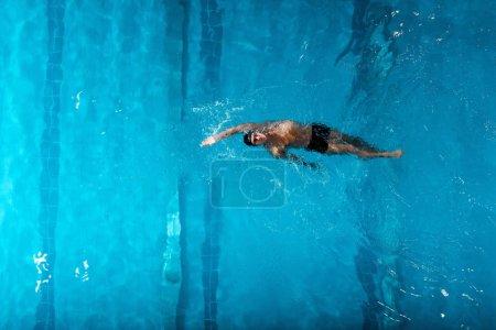 Photo pour Vue de dessus du beau nageur faisant dos nageant dans la piscine - image libre de droit