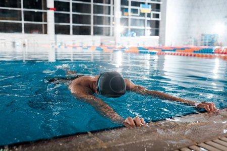 Photo pour Homme en bonnet de bain étirant dans l'eau - image libre de droit