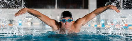 Photo for Panoramic shot of handsome swimmer swimming butterfly stroke in swimming pool - Royalty Free Image