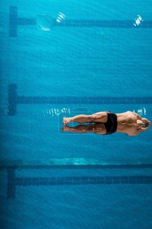 Photo pour Vue de dessus du nageur musculaire plongeant dans l'eau - image libre de droit