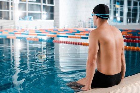 Photo pour Sportif musclé en bonnet de bain assis près de la piscine - image libre de droit
