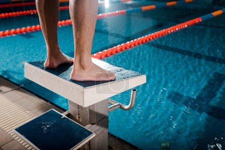Photo pour Vue recadrée du sportif debout sur un bloc de plongée près de la piscine - image libre de droit
