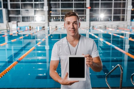 Photo for Cheerful trainer holding digital tablet with blank screen - Royalty Free Image