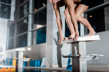 Photo for Cropped view of sportsman standing in starting pose on diving block - Royalty Free Image