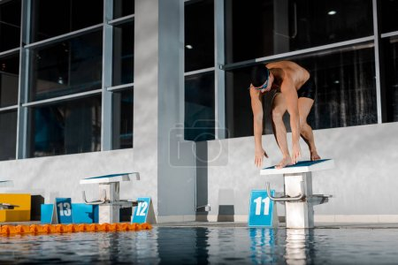 Photo for Sportsman standing in starting pose near swimming pool - Royalty Free Image