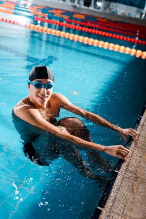 Photo for Happy swimmer in goggles smiling while looking at camera in swimming pool - Royalty Free Image
