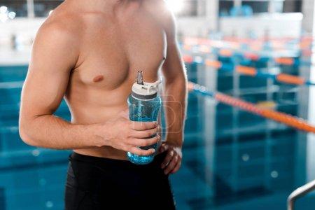 Photo pour Vue recadrée d'un sportif musclé tenant une bouteille de sport près de la piscine - image libre de droit