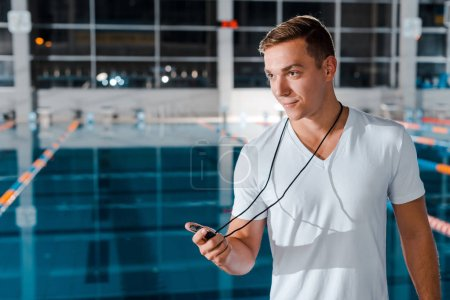 happy trainer holding timer near swimming pool