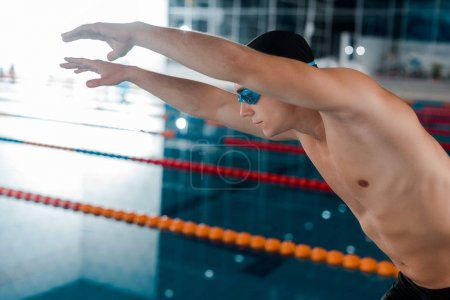 Photo for Handsome and muscular swimmer in goggles with outstretched hands - Royalty Free Image