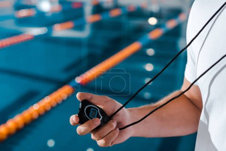 Photo for Cropped view of trainer holding timer near swimming pool - Royalty Free Image