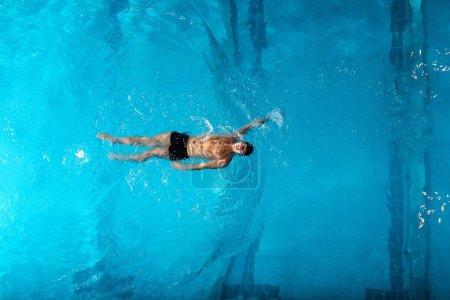 Photo pour Vue de dessus du sportif dans les camions de natation formation dans la piscine - image libre de droit