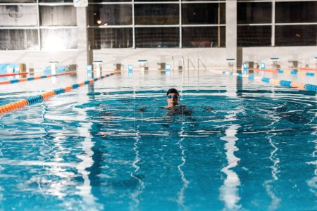 Photo for Swimmer in goggles training in swimming pool - Royalty Free Image