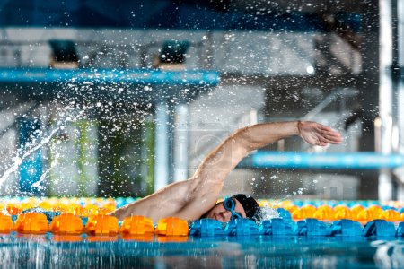 Photo pour Des gouttes d'eau près d'un beau nageur s'entraînent dans une piscine - image libre de droit
