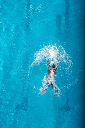Photo for Top view of swimmer diving into water in swimming pool - Royalty Free Image