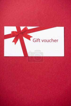 Photo pour Vue du dessus du bon cadeau sur fond rouge avec espace de copie - image libre de droit