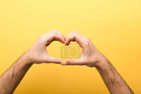 Photo pour Crochet vue d'un homme montrant un geste de cœur sur fond jaune - image libre de droit