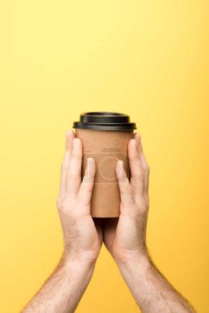 Photo pour Vue recadrée de l'homme tenant une tasse en papier sur fond jaune - image libre de droit