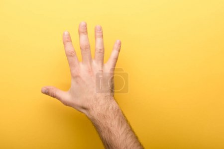 Photo for Cropped view of man showing five fingers on yellow background - Royalty Free Image