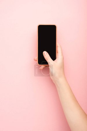 Photo for Cropped view of woman holding smartphone on pink background - Royalty Free Image