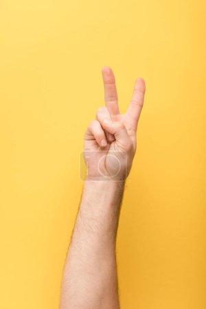 Photo pour Vue recadrée de l'homme montrant un geste de paix sur fond jaune - image libre de droit