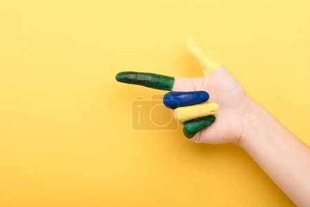 Photo for Cropped view of woman pointing with finger on yellow background - Royalty Free Image