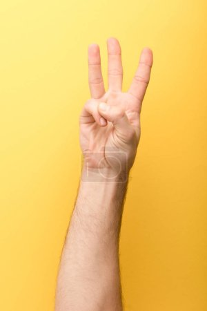 Photo for Cropped view of man showing three fingers on yellow background - Royalty Free Image