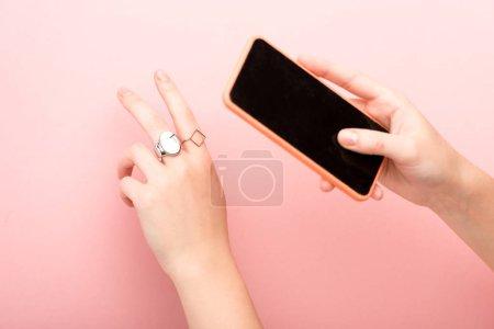 Photo pour Crochet vue d'une femme montrant la paix et prenant une photo sur fond rose - image libre de droit