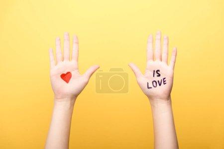 Photo pour Crocheté vue d'une femme montrant des paumes avec cœur et est amoureux lettrage isolé sur jaune - image libre de droit