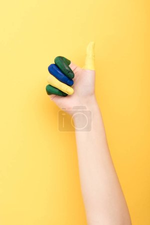 cropped view of woman with colorful fingers showing like on yellow background
