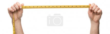 Photo for Panoramic shot of man holding measuring tape isolated on white - Royalty Free Image