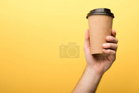 cropped view of man holding paper cup on yellow background