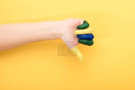 vista recortada de la mujer con los dedos de colores que muestran aversión sobre el fondo amarillo