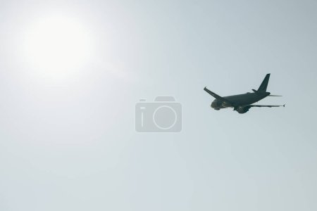 Photo pour Low angle view of aeroplane in clear sky with sun - image libre de droit