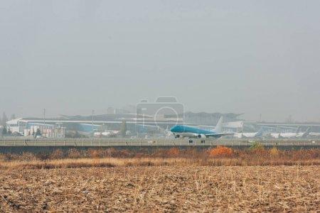 Photo pour Avion commercial sur piste dans un champ avec ciel nuageux en arrière-plan - image libre de droit