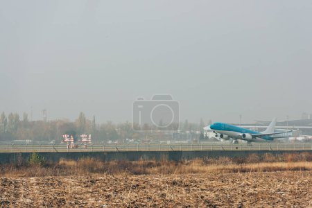 Photo for Flight departure of airplane on airfield with cloudy sky at background - Royalty Free Image