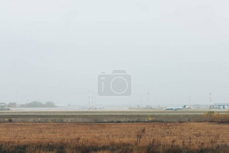 Photo pour Airplane on runway in field with cloudy sky at background - image libre de droit
