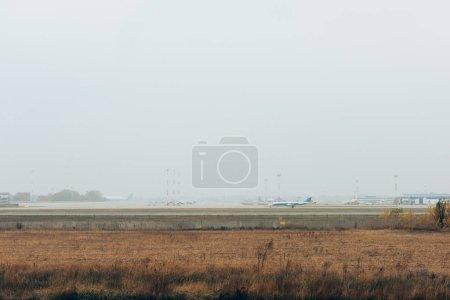 Photo pour Avion sur piste de l'aéroport avec ciel nuageux en arrière-plan - image libre de droit