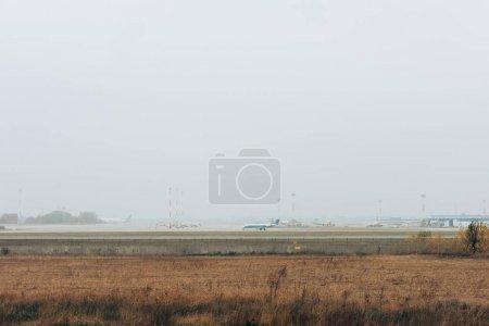 Photo pour Terrain gazonné avec avion sur la piste et ciel nuageux - image libre de droit