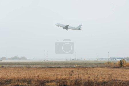 Photo pour Aéronefs atterrissant au-dessus d'un terrain d'aviation ensoleillé avec ciel nuageux - image libre de droit