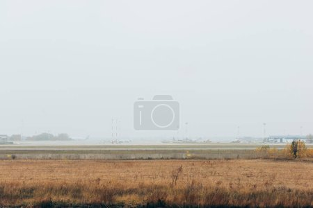 Photo for Grassy airfield with commercial planes on highway - Royalty Free Image