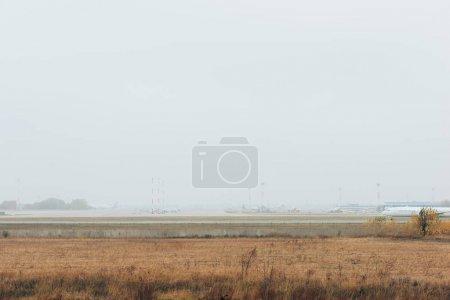Photo pour Avion commercial sur piste d'aéroport avec ciel nuageux - image libre de droit